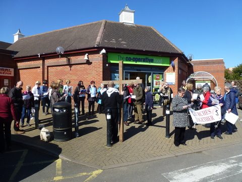 The joint churches singing hymns outside the Co-Op store